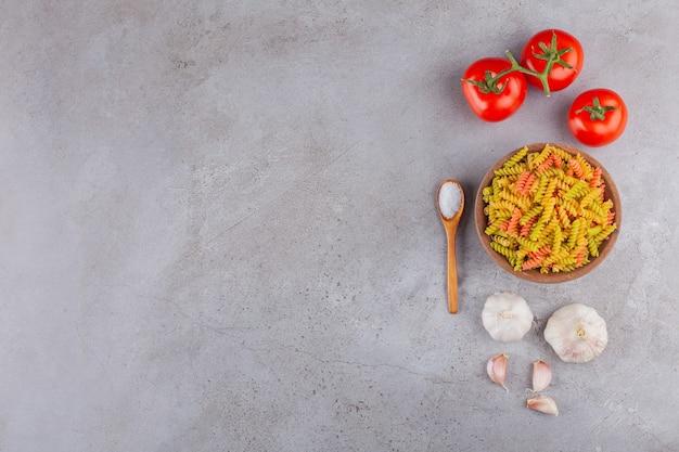 마늘과 신선한 빨간 토마토와 멀티 컬러 원시 나선형 파스타의 점토 그릇.