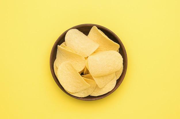 노란색 배경에 감자 칩이 있는 점토 그릇. 인기있는 감자 요리. 플랫 레이.
