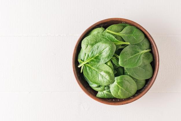 흰색 나무 테이블에 시금치가 든 점토 그릇. 건강을 위한 음식. 채식주의 자 음식. 정상에서 본 모습.