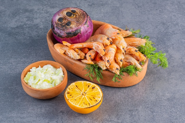 Глиняная тарелка вкусных креветок с нарезанным лимоном и луком на каменной поверхности