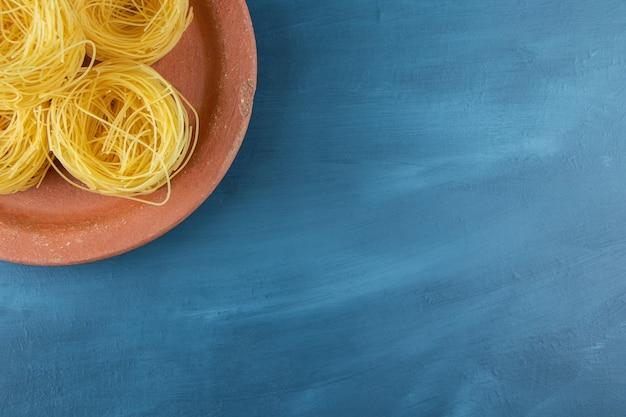 Глиняная тарелка сырых сухих макарон для гнезда на темно-синем фоне.