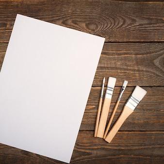 Чистый белый лист и кисти на текстурированном фоне с пространством для копирования. макет, макет места для текста и рисунка.