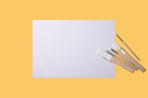 Чистый белый лист и кисти на желтом фоне с местом для копирования. макет, макет, верстка.