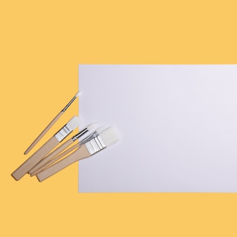 Чистый белый лист и кисти на желтом фоне с местом для копирования