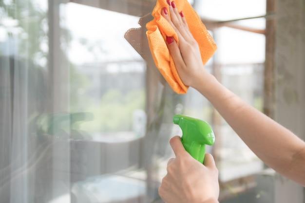 清掃会社が窓の汚れをきれいにします。主婦は家の窓をクリーナーで磨く