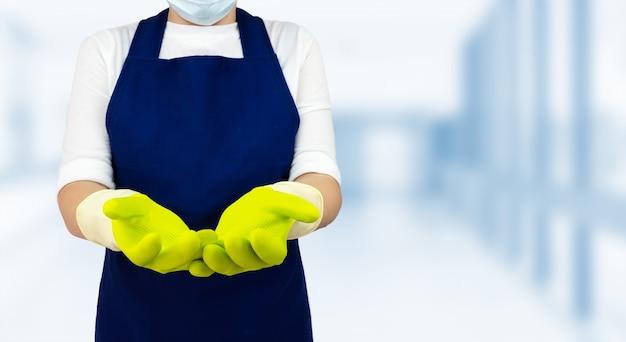 Уборщица в зеленых перчатках на размытом фоне. концепция очистки и дезинфекции
