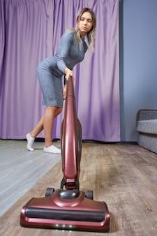 Уборщица пылесосит пол вертикальным пылесосом или электрической щеткой.