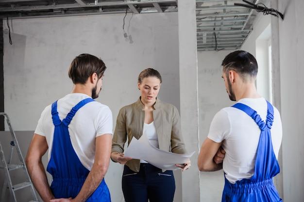 Клиент держит план дома. она разговаривает с двумя мужчинами в форме