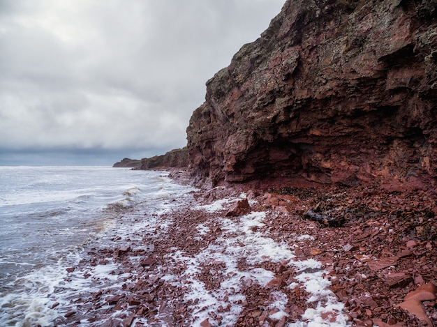 海岸線が狭い海に面した崖。岩の多い海岸に白い泡のある波が転がっています。テルスキー海岸、コラ半島へのケープ船。