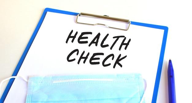 医療用保護マスク付きのクリップボードがテーブルの上にあります。碑文ヘルスチェック。医療の概念。