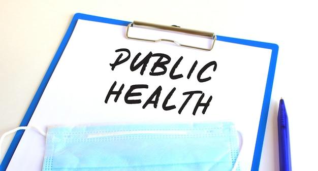 医療用保護マスク付きのクリップボードがテーブルの上にあります。碑文公衆衛生。