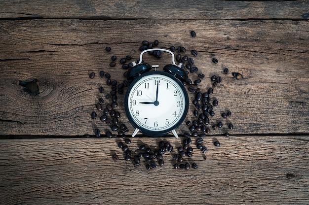 Часы и кофейные зерна на столе сверху