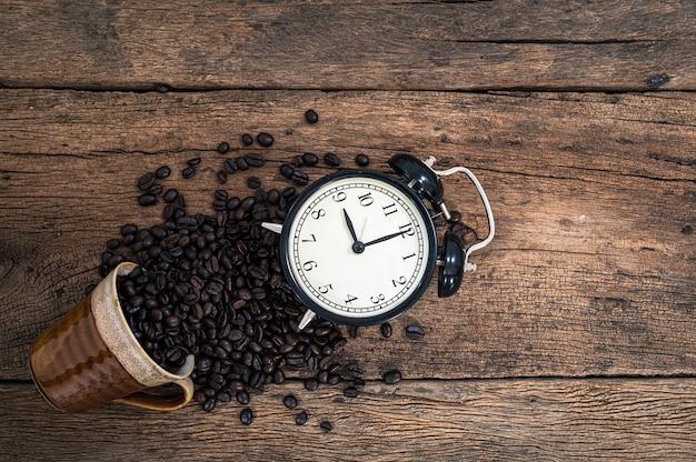 Часы и кофейные зерна на столе, вид сверху