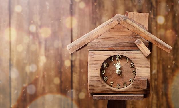 家の形をした時計は、木製の壁の背景に真夜中を示しています
