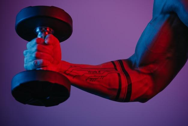 青と赤のライトの下でダンベルで上腕二頭筋のカールをしている筋肉の腕のクローズ写真