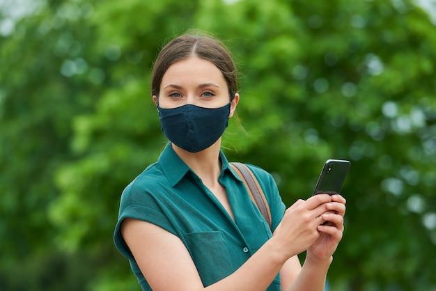 의료 얼굴 마스크에 여자의 가까운 초상화는 공원에서 산책하는 동안 스마트 폰을 들고있다