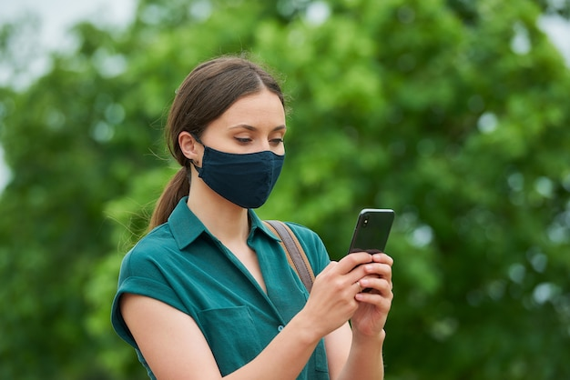 의료 얼굴 마스크에 여자의 가까운 초상화는 공원에서 산책하는 동안 스마트 폰 뉴스를 읽고있다