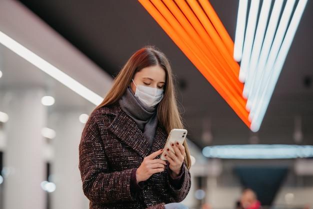 医療用フェイスマスクをかぶった女性の身近な肖像画が、スマートフォンを持って地下鉄の駅に座ってニュースを読んでいます。サージカルマスクをした女の子が地下鉄で社会的距離を保っています。