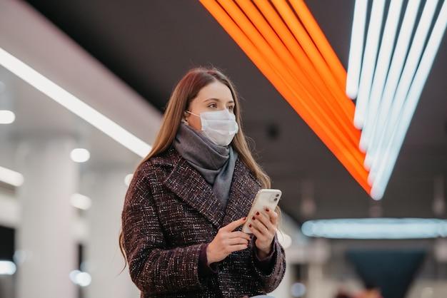 医療用フェイスマスクをかぶった女性の身近な肖像画が、スマートフォンを持って地下鉄の駅に座って電車を待っています。サージカルマスクをした女の子が地下鉄で社会的距離を保っています。