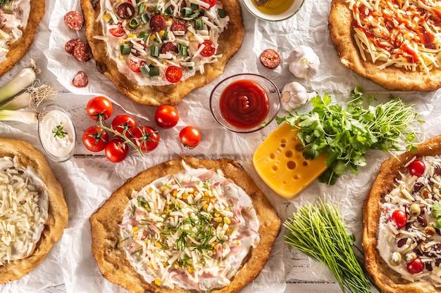 Закройте набор традиционных венгерских ланго с хрустящими чесночными краями, которые подают с овощами, сливочными сосисками, зеленью, тертым сыром, кетчупом и соусами.