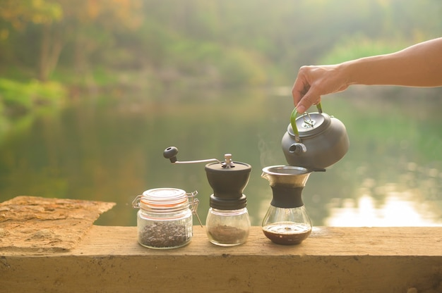 Крупным планом капает кофе на фоне природы, расслабиться концепция путешествия