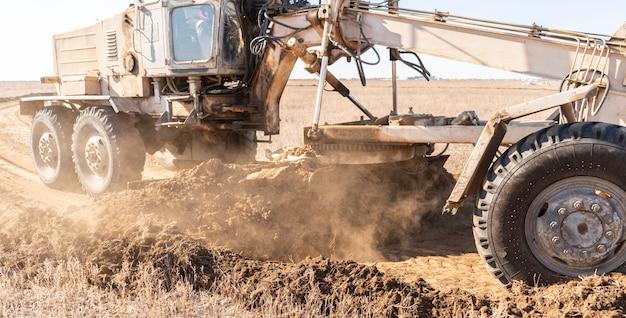 가까이 학년 국자가 여름날 흙을 파 내고 난간을 만듭니다.