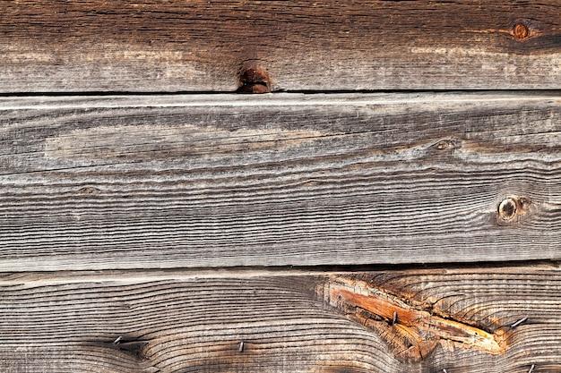 Крупный план поврежденной деревянной поверхности - обнесенного стеной дома в деревне.