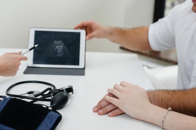 クローズアップ-医師との診察中のタブレット上の赤ちゃんの超音波のアップ画像。薬。