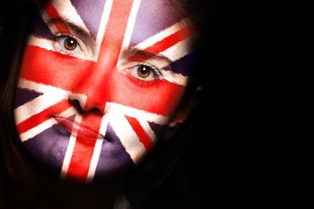 Крупный план британского флага на женском лице на темном фоне