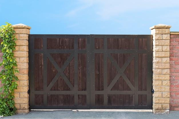 맑고 푸른 하늘 배경에서 어두운 나무 폐쇄 게이트 드라이브를 닫습니다. 시골집의 입구 게이트입니다. 드라이브 어웨이 게이트 디자인 아이디어. 벽돌로 된 울타리에 목재 게이트입니다. 게이트 건설.
