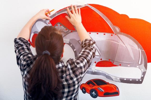 여성 예술가의 클로즈업은 어린이 방에 흰 벽에 자동차의 그림을 그립니다