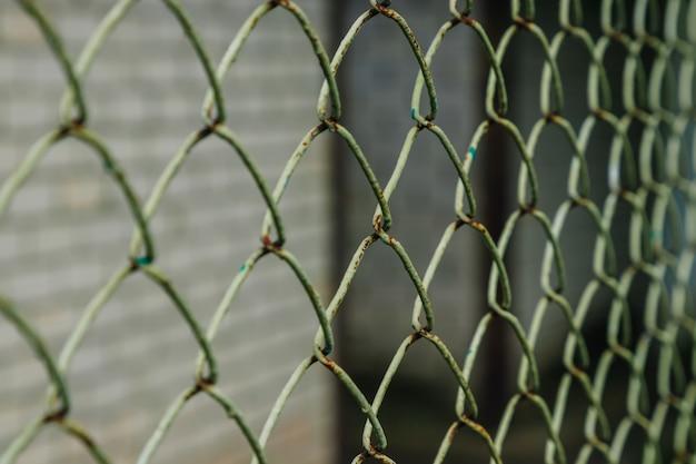 斜めの緑のチェーンリンクフェンスのクローズアップ。