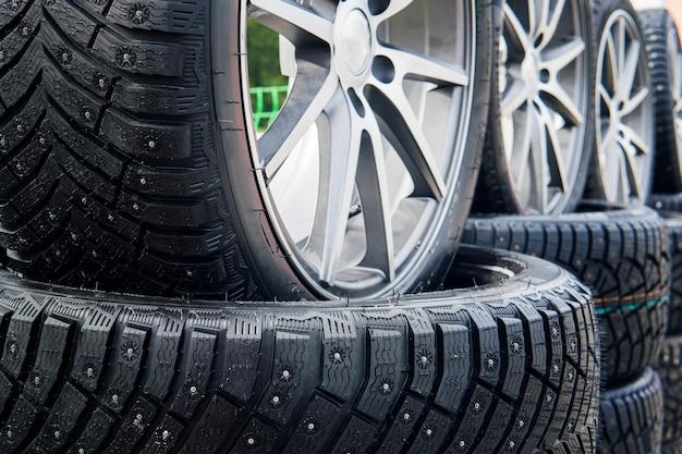 Крупным планом - зимние шипованные колеса с подкладкой, установленные на открытом воздухе. крупным планом - шипы и протекторы на шинах, установленных на улице. зимние шины устанавливаются на открытом воздухе. ряды открытых зимних шин.
