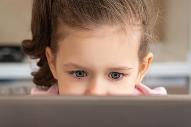 Крупным планом маленькая девочка, глядя на ноутбук или планшет с копией пространства