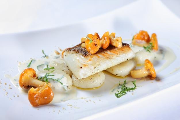 Крупный план порции рыбы с лисичками, подаваемой с соусом на белой тарелке