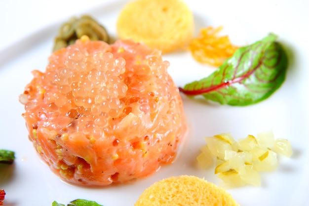 Крупный план порции татарского лосося с икрой на белой тарелке