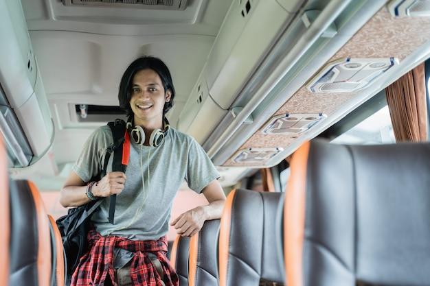 バスの座席の間に立っているバックパックとヘッドフォンを身に着けている笑顔の若い男のクローズアップ