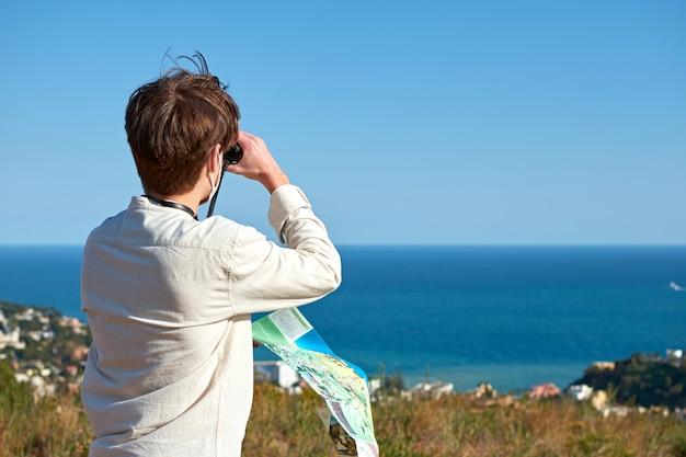 Крупный план исследователя из испании в белой рубашке, наблюдающего за прибрежным городом в бинокль по карте.
