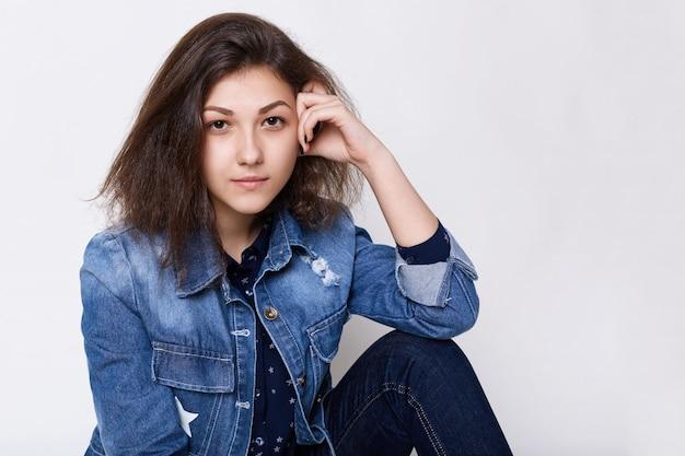 自信を持って非常に注意深く見ているジーンズのジャケットを着ている魅力的な茶色の瞳の少女のクローズアップ