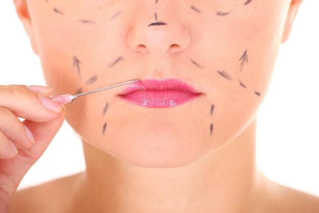 女性の唇と白い背景の針のクローズアップ