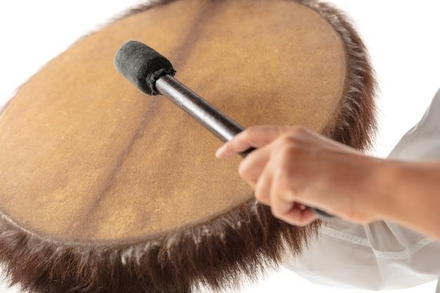 흰색 스튜디오 배경에서 탬버린 타악기를 연주하는 손 클로즈업