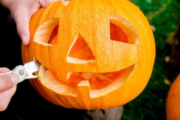 Крупный план руки мужчины, который режет ножом тыкву и готовит фонарь из тыквы. хэллоуин. украшение для вечеринки.