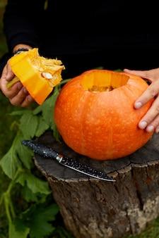 ジャック・オランタンを準備する間、男の手のクローズアップがカボチャから蓋を切りました。ハロウィン。パーティーのための装飾。
