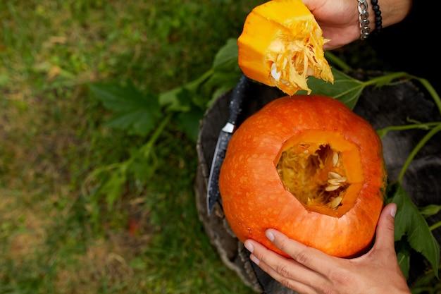 Крупным планом - рука человека срезает крышку с тыквы, когда он готовит джека олантерна. хэллоуин. украшение для вечеринки.