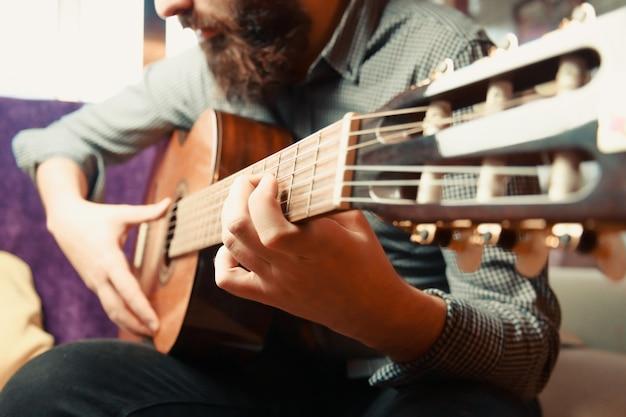 A 밝은 하루 동안 스페인 기타를 연주하는 수염 난 남자의 손을 가까이