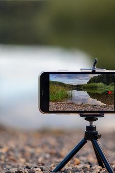 삼각대에 전화기를 가까이 대면 자연의 비디오나 사진이 찍힙니다. 사진 작가의 휴대 전화 화면에 구름이 있는 숲의 아름다운 호수.
