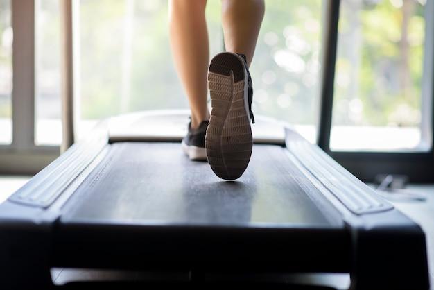 A 피트니스 체육관에서 실행 기계 또는 디딜 방아에 여자 주자 신발 닫습니다