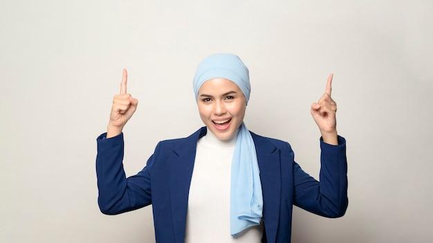 白い壁に分離されたヒジャーブと若い美しいイスラム教徒の実業家のクローズアップ