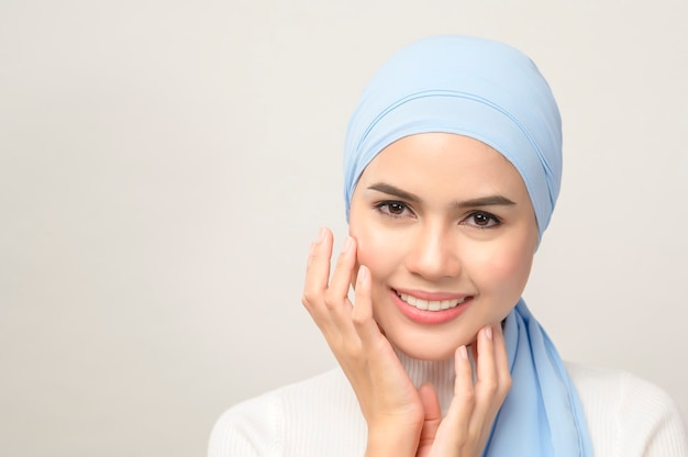 白い背景のスタジオ、イスラム教徒の美しさのスキンケアの概念に分離されたヒジャーブを持つ若い美しいイスラム教徒の女性のクローズアップ。