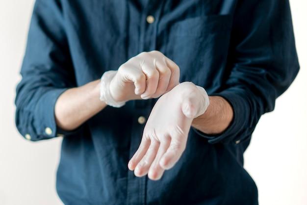 クローズアップの人は、コロナビダスの流行から保護するために手に保護手袋を着用しようとします